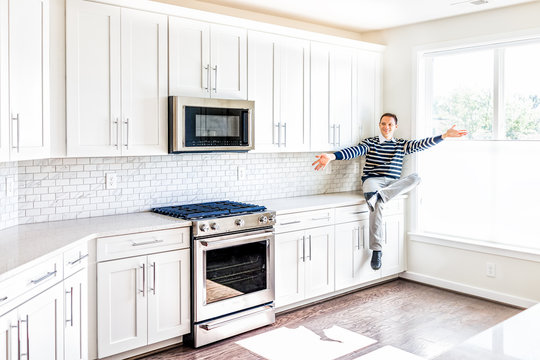 Young man sitting on kitchen countertop with outstretched open arms in clean, modern, white home design