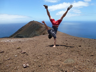 One-armed handstand on a volcano in font of the sea on the island of La Palma