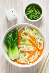 Vegetarian Asian rice noodle soup with bok choy, carrots and spring onion, photographed overhead with natural light (Selective Focus, Focus on the top of the soup)