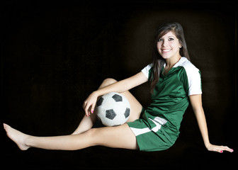 A soccer teenager player posing for a portrait with her ball in a black background