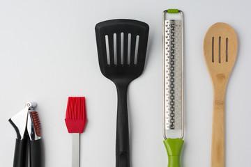 Garlic Press Brush Spoon Spatula Zester on White Background Cropped Close