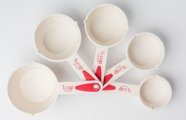 Set of Fanned Measuring Cups on White Background Top View