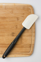 Silicone Spatula Angled on Wooden Cutting Board on White Background