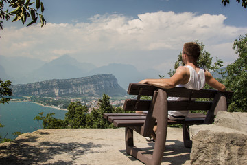 boy sitting on the bench, on the rock of the mountain looks at the landscape