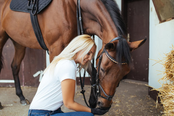 Beautiful young woman enjoying with her horse outdoors at ranch.
