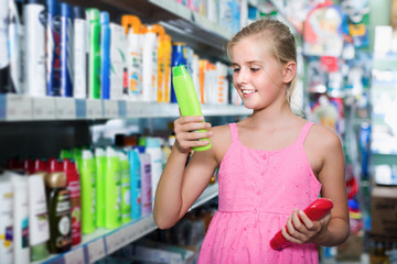 Portrait of girl teenager holding shampoo and conditioner