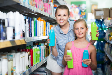 smiling female with daughter holding shampoo