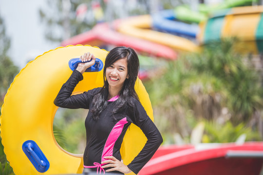 happy young woman with tube in a water park resort