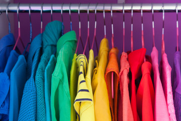 Various clothes are hung on hangers in the closet. Bright colors of the rainbow.