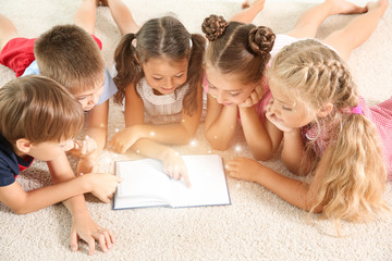Cute little children reading book on floor