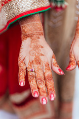 Henna paint on hand for woman at Indian wedding ceremony in Bangkok, Thailand.