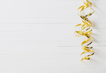 golden ribbon on white wooden background