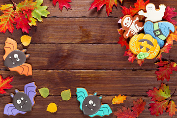 Beautiful festive background for Halloween with gingerbread, candy, autumn leaves and berries on a wooden table. Free space