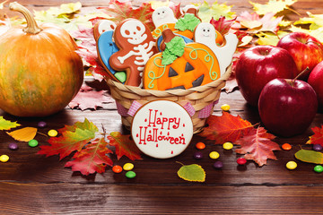 Beautiful festive background for Halloween with basket gingerbread, autumn leaves, berries and candy on a wooden table. Happy Halloween. Free space