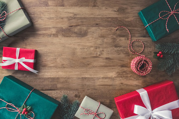 Top view of Christmas gift boxes on a wooden table with pine and mistletoe