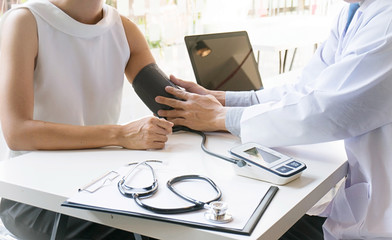 Doctor checking old woman patient arterial blood pressure. Health care