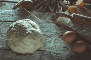Dough, rolling pin and wheat ears on wooden background floured