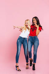 Full-length image of two happy women pointing and looking away