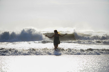 silhouette of young happy Asian woman relaxed looking at wild sea waves on sunset tropical beach