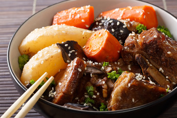 Spicy ribs stewed with mushrooms, pears and carrots close-up in a bowl. horizontal