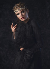 Queen of darkness in black fantasy costume on dark gothic background. High fashion beauty model with dark makeup.