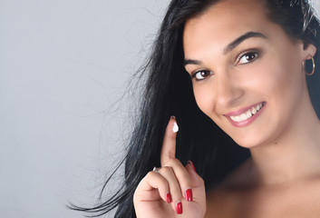 portrait of beautiful young woman applying some cream to her face for skin care