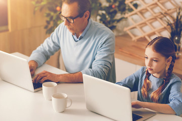 Father and daughter refusing to chat while using laptops