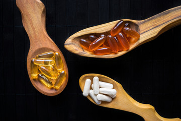 Nutritional supplements and vitamins for brain in three wooden spoons on a dark background. Variety of dietary supplements, gel capsules and Veggie Caps of Omega 3 Fish Oil, lecithin, ginkgo biloba