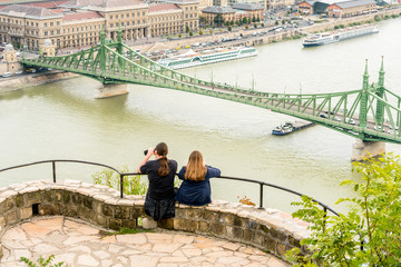 A young couple sitting at a viewpoint up high taking pictures of Liberty bridge over the Danube river, Budapest Hungary.