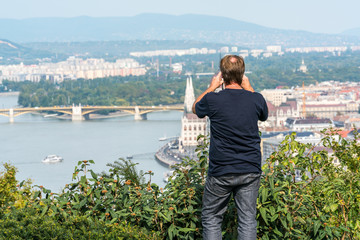 A man standing in green bushes up high at a viewpoint to take a panoramic picture Budapest below.