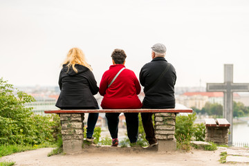 Back view of two overweight woman and one older man sitting on a bench looking out over Budapest Hungary.