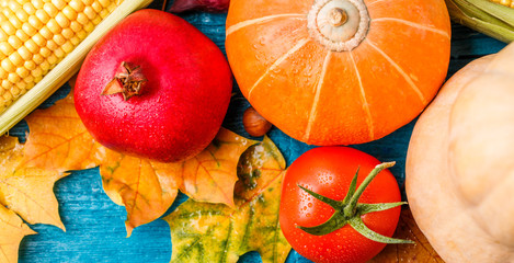 Image from above of autumn leaves, pumpkin, tomato, pomegranate, corn