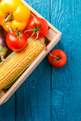 Picture on top of wooden box with corn, pepper, tomato