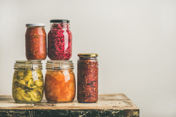 Autumn seasonal pickled or fermented colorful vegetables in glass jars placed in stack over vintage kitchen drawer, white wall background, copy space. Fall home food preserving or canning