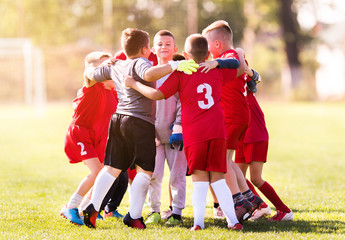 Kids soccer football - children players celebrating after match on soccer field