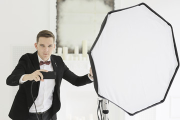 man Photographer professional in studio with flash and phone