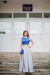 Portrait of an attractive girl standing and posing on the stairs in amazing gowns after high school graduation.