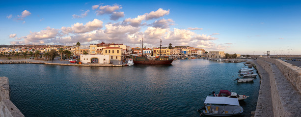 Venetian Harbour panorama with boats in front of restaurants at sunrise under colored clouds. Rethymno, Greece
