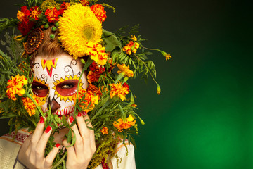 Женщина с разрисованным лицом к мексиканскому Дню Мертвых с цветами на зеленом фоне.