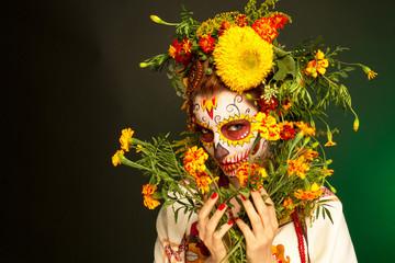 Женщина с разрисованным лицом к мексиканскому Дню Мертвых с цветами на темно-зеленом фоне.