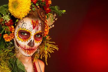 Женщина с разрисованным лицом к мексиканскому Дню Мертвых с цветами на красном фоне.