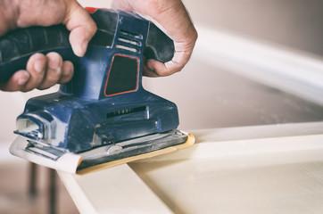 Orbital sander in use, sanding old door for a new lick of paint.