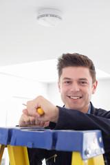 Man Installing Smoke Or Carbon Monoxide Detector