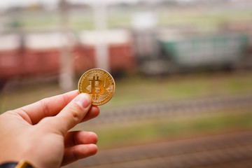 Hand holding golden bitcoin virtual money train
