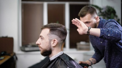 Young barber standing and making stylish haircut of attractive man with clipper in barbershop. Bearded man is sitting on the chair with black protective cape against the mirror and looking at himself.