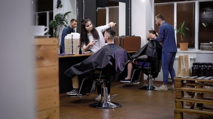 The process of hair cutting in barbershop, several hairdressers make stylish and fashionable hairstyles in the men's beauty salon