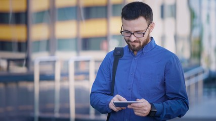 Handsome bearded man with bag across his shoulder in blue shirt and brown trousers is standing typing messages using his smartphone. Young businessman is waiting for friends with digital gadget.
