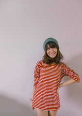 A fashion portrait of young hipster asian woman wearing sweater and beanie knit hat