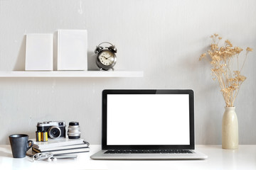 Mockup copy space blank screen laptop and office supplies on white desk. Stylish workspace concept.