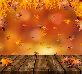 Maple Leaves with wooden Table and beautiful Autumn Background